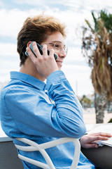young guy talking on the phone outside