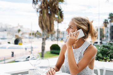 young girl talking on the phone sitting at a restaurant table