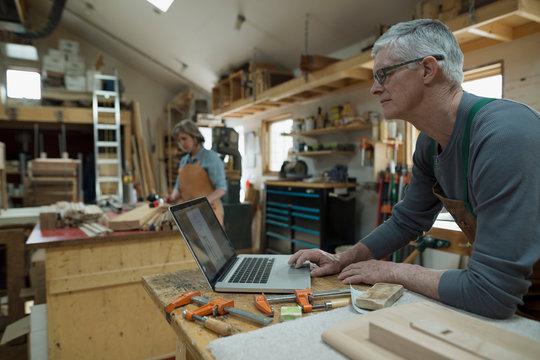 Carpenter working at laptop in workshop