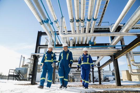 Workers walking below gas plant pipeline