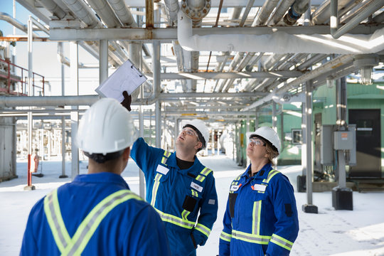Workers looking up inspecting gas plant pipelines