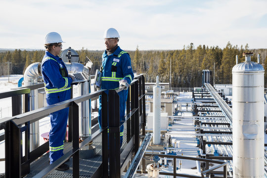 Engineers with laptop talking platform above gas plant
