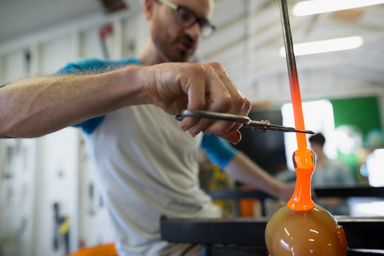 Glassblower clipping molten glass with scissors in workshop