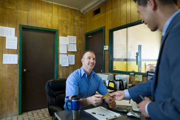 Customer paying mechanic in auto repair shop office