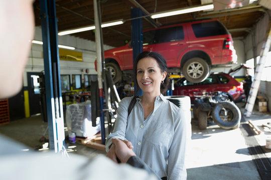 Customer and mechanic shaking hands auto repair shop
