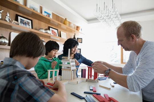 Family playing with building clocks at dining table