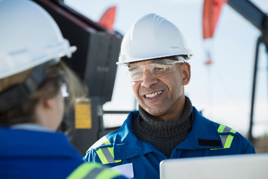 Smiling engineer talking to coworker at gas plant
