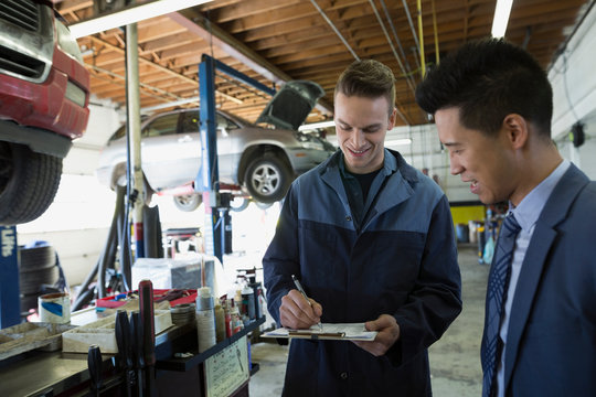 Mechanic and customer talking in auto repair shop