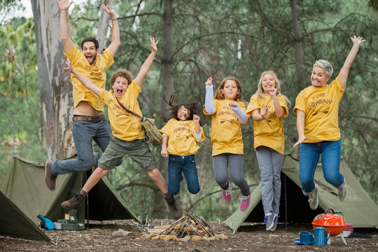 Portrait of happy camp counselors and children jumping together in forest