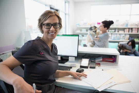 Portrait smiling veterinarian at clinic reception desk