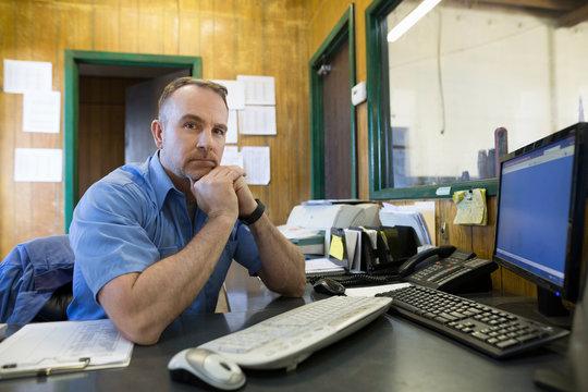 Portrait confident mechanic at computer auto shop office