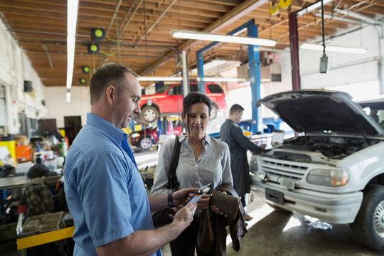 Customer paying mechanic credit card auto repair shop
