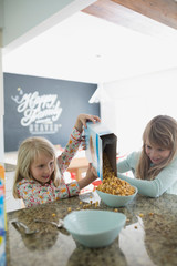 Sisters pouring cereal for breakfast in kitchen