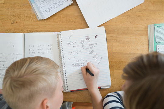 Overhead view of mother helping son with math homework
