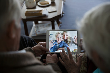 Senior couple video chatting with daughter and grandson on digital tablet