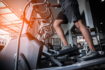 Keuken foto achterwand Fitness young man working out on an elliptical trainer in gym