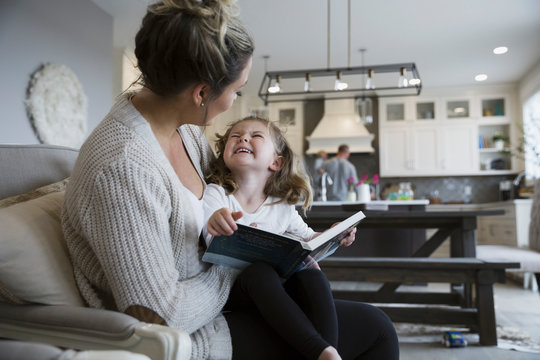 Mother and laughing daughter reading book on living room sofa