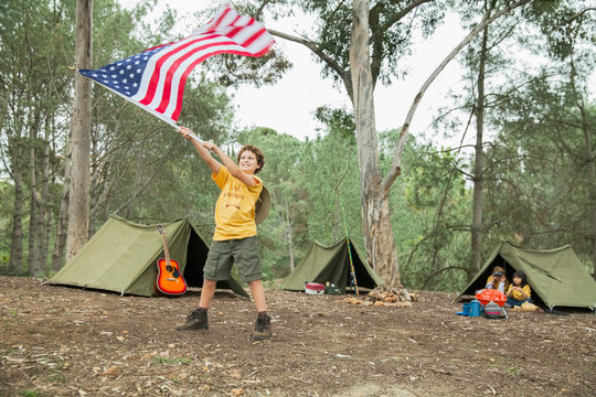 Boy waving American flag in forest while camping