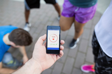 Man checking heart rate with cell phone app in running group