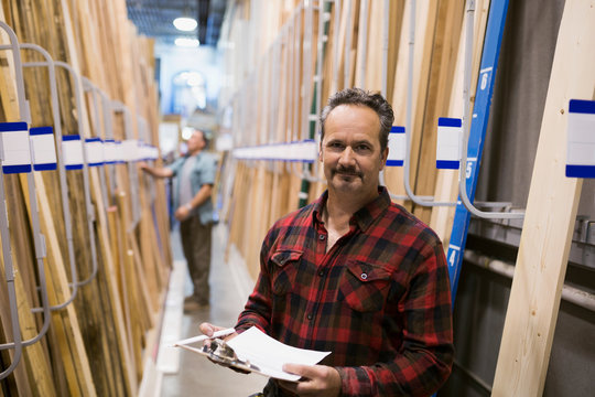 Portrait smiling worker with clipboard in home improvement store