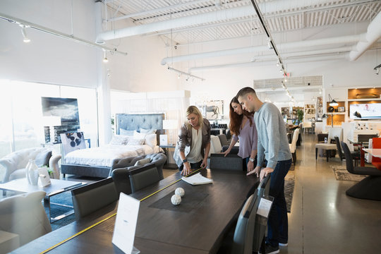 Interior designer and couple measuring dining table in home furnishings store