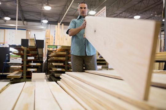 Man examining wood planks at home improvement store