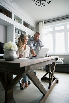 Couple working at laptop in home office