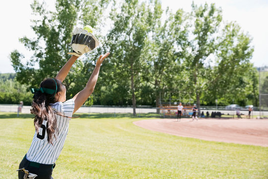 Middle school girl softball player catching softball in outfield