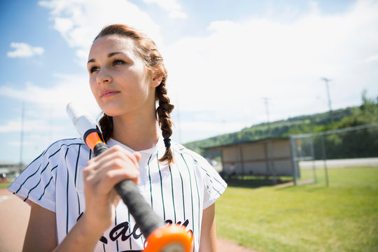 Serious middle school girl softball player holding bat on sunny field