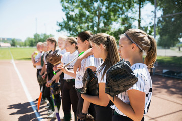 Middle school girl softball team standing in a row watching game