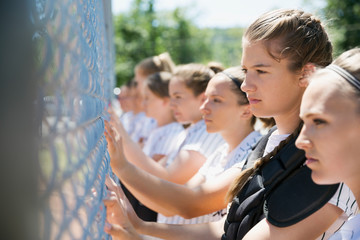 Middle school girl softball team standing in a row at fence