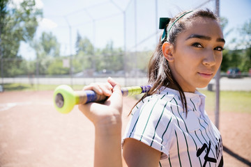 Portrait confident middle school girl softball player holding bat