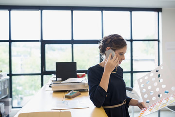 Female designer talking on cell phone looking at brochure in office