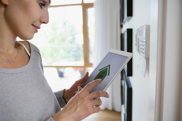 Woman setting alarm with home security app on digital tablet