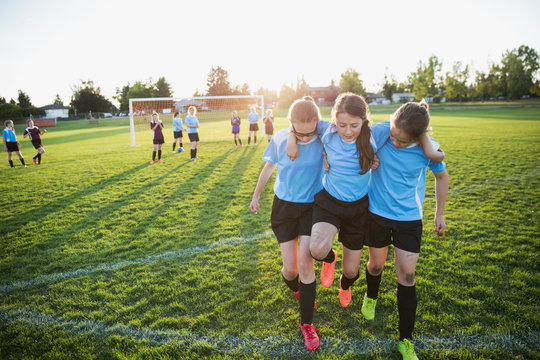 Middle school girl soccer players helping injured teammate off field