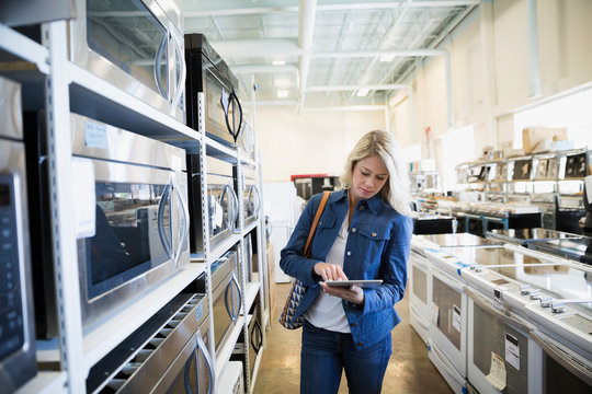 Woman with digital tablet shopping for microwave in appliance store