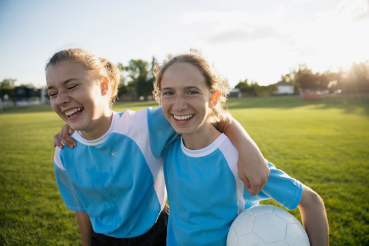 Portrait laughing middle school girl soccer teammates hugging on field