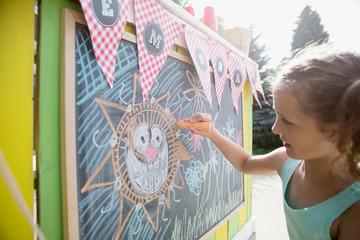 Girl drawing sun on lemonade stand blackboard with chalk