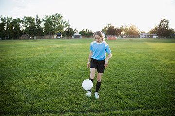 Middle school girl soccer player practicing juggling soccer ball on field