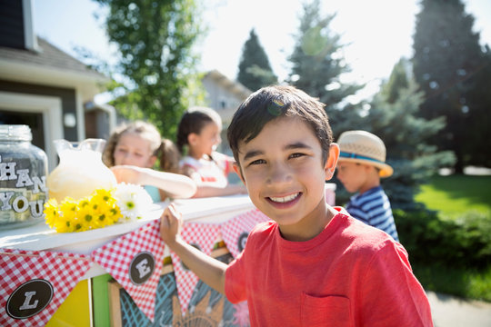 Portrait smiling boy at lemonade stand in sunny driveway