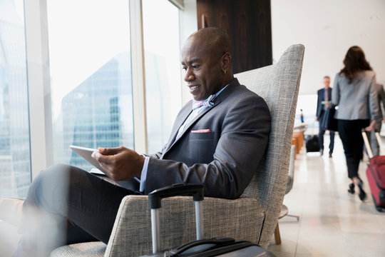 Businessman with luggage using digital tablet in airport lounge