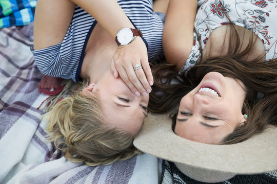 Female friends whispering and laughing on blanket