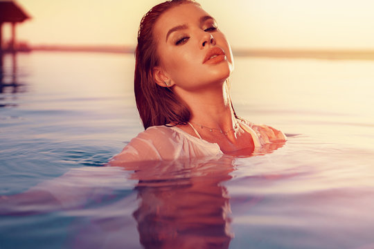 Young woman beauty portrait in water in sunset