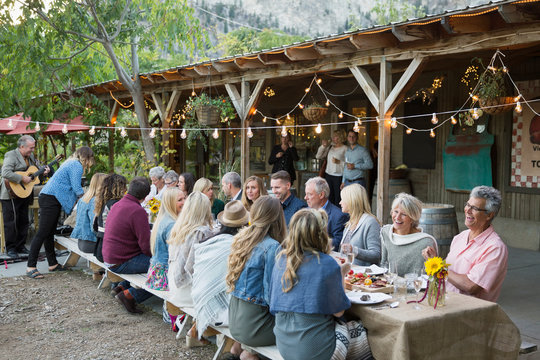 Friends enjoying outdoor harvest dinner party at long patio table