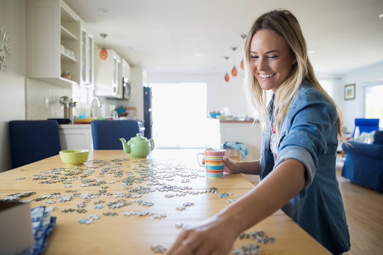 Young woman assembling jigsaw puzzle at dining table