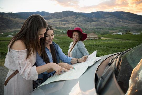 Women friends looking at map on automobile hood in vineyard