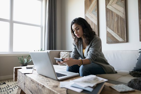 Young woman with laptop and calculator paying bills online on living room sofa