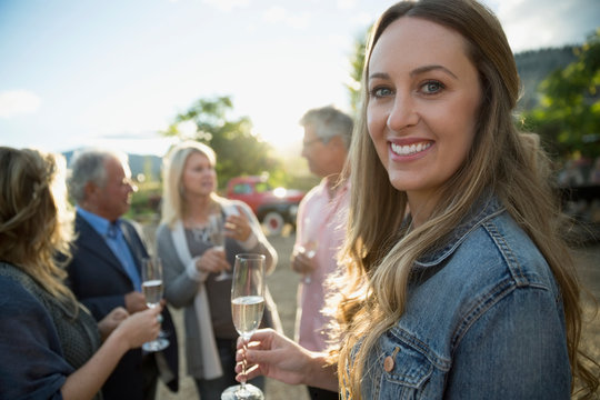 Portrait smiling woman drinking champagne with friends at vineyard