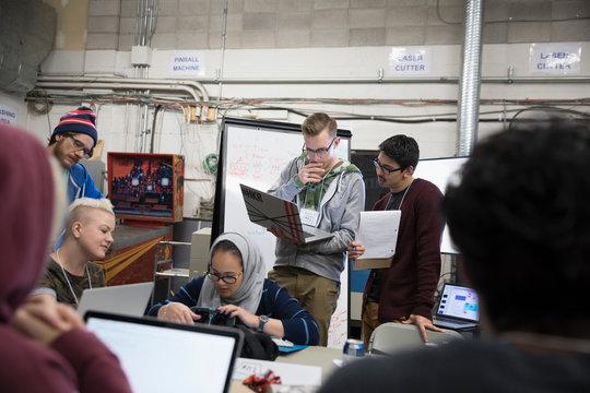 Hacker teams brainstorming working hackathon at laptops in workshop