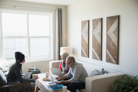 Financial advisor meeting with senior couple using laptop in living room